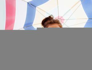 Vai à praia  Saiba tudo sobre óculos de sol. Woman in sunglasses holding  beach umbrella ... a256110842